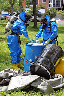 Environmental in protective suits work on chemical drums in the field.