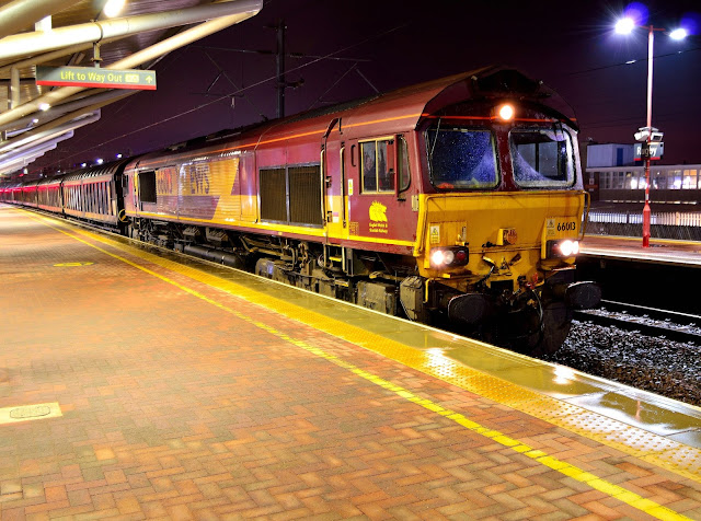 Night Photo of EWS liveried Class 66013 stops at Rugby station during a rain shower in 2016