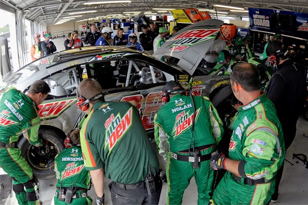 Crew members work on the car of Dale Earnhardt Jr., driver of the #88 Diet  Mountain Dew Chevrolet