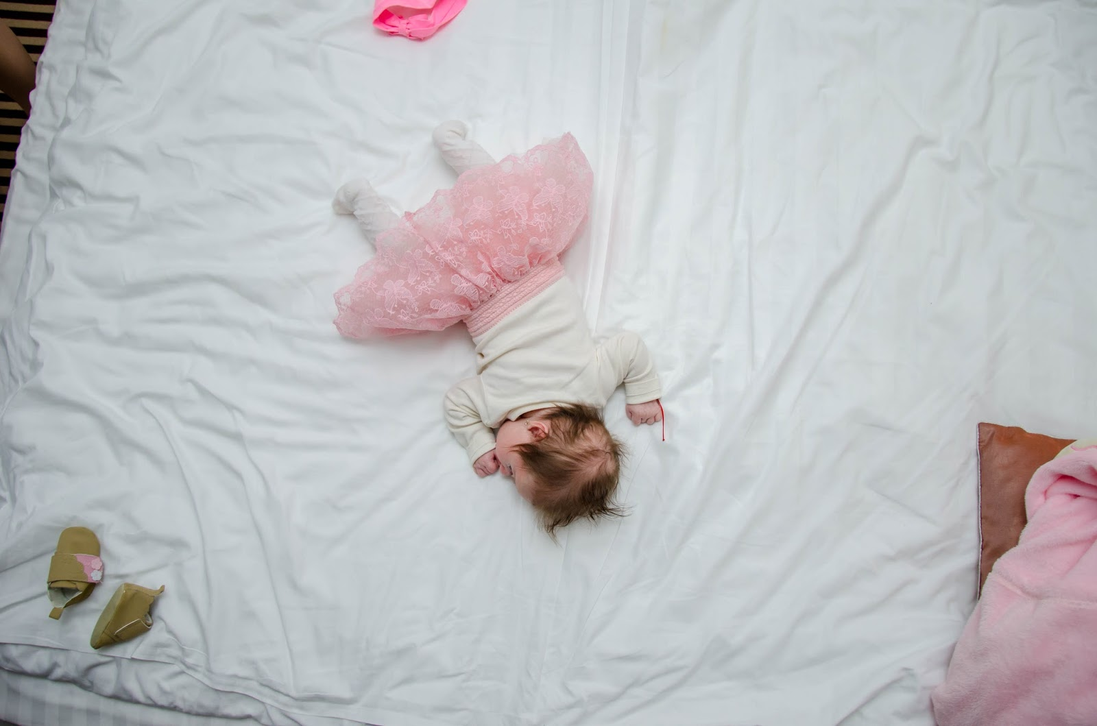 Baby girl in a pink tutu sleeping on a big white double bed
