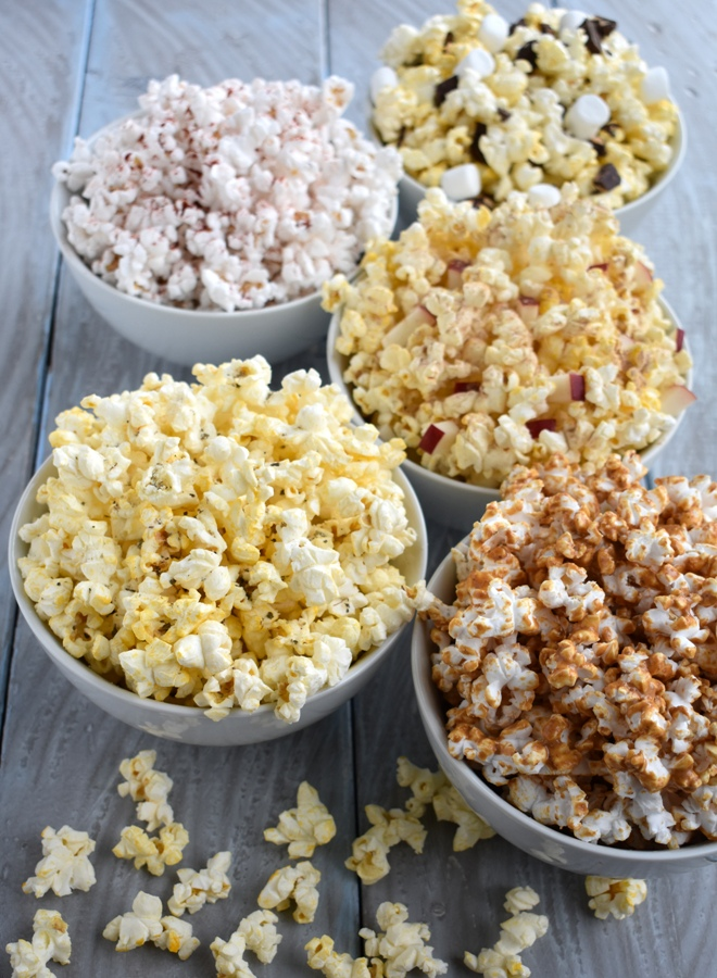 5 healthier popcorn mix-ins for a fun and delicious snack: peanut butter popcorn, garlic bread popcorn, apple cinnamon popcorn, s'mores popcorn and smoky BBQ popcorn. www.nutritionistreviews.com