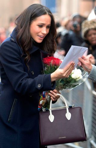 Meghan Markle Wearing Strathberry Midi Tote in Burgundy/Navy/Vanilla while accepting gifts from Public including flowers