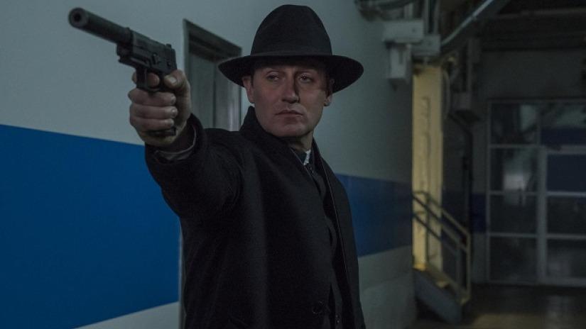 John Pilgrim (Josh Stewart) hangtompítós fegyverrel, kalapban