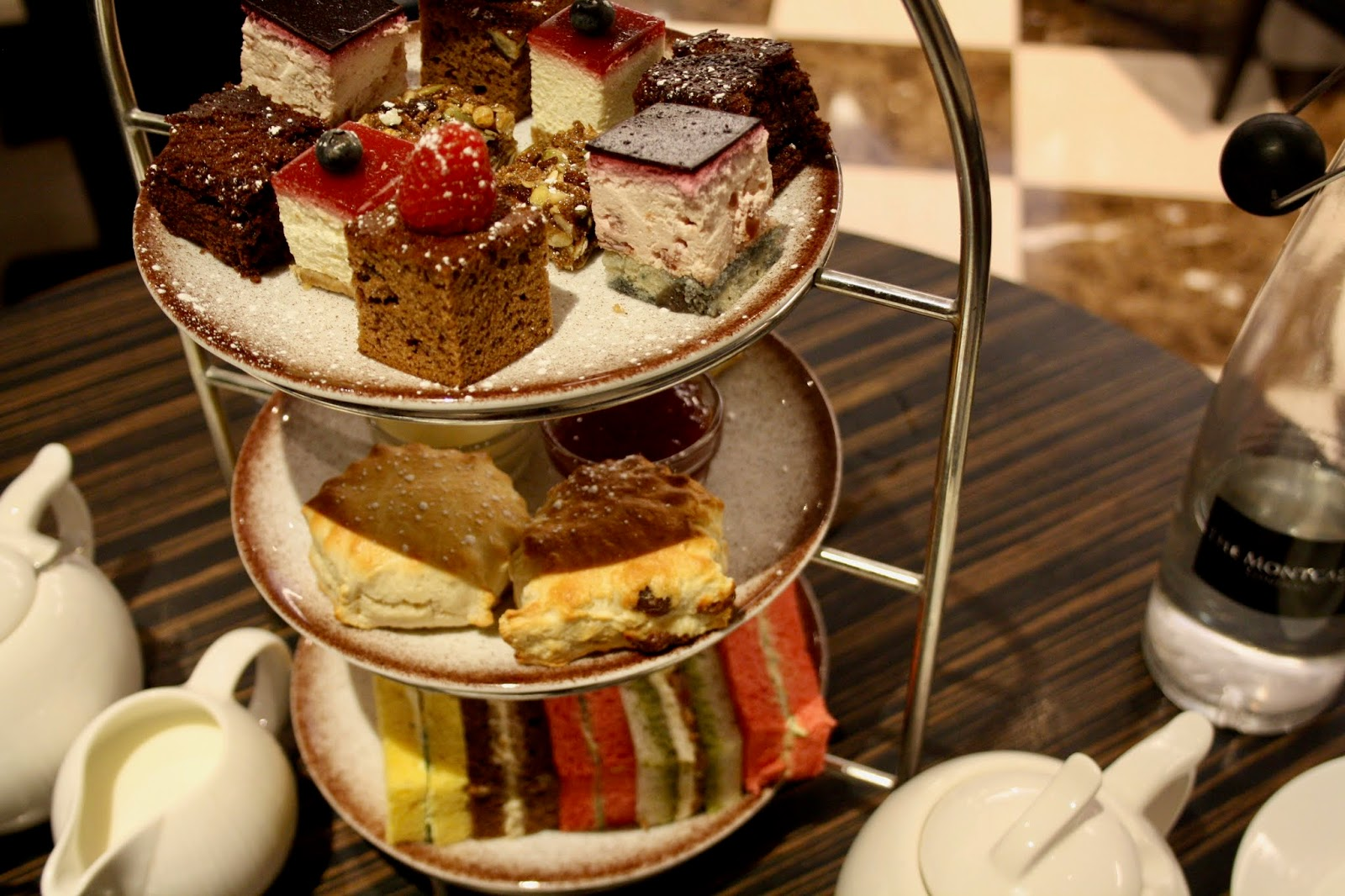 Tier of afternoon tea including sandwiches, scones, and cakes