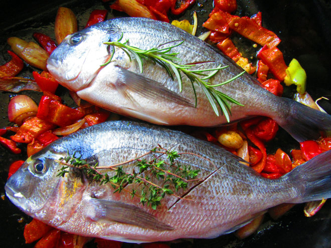 Gilt-head bream with romesco sauce by Laka kuharica: place the fish on top of the vegetables, drizzle with olive oil