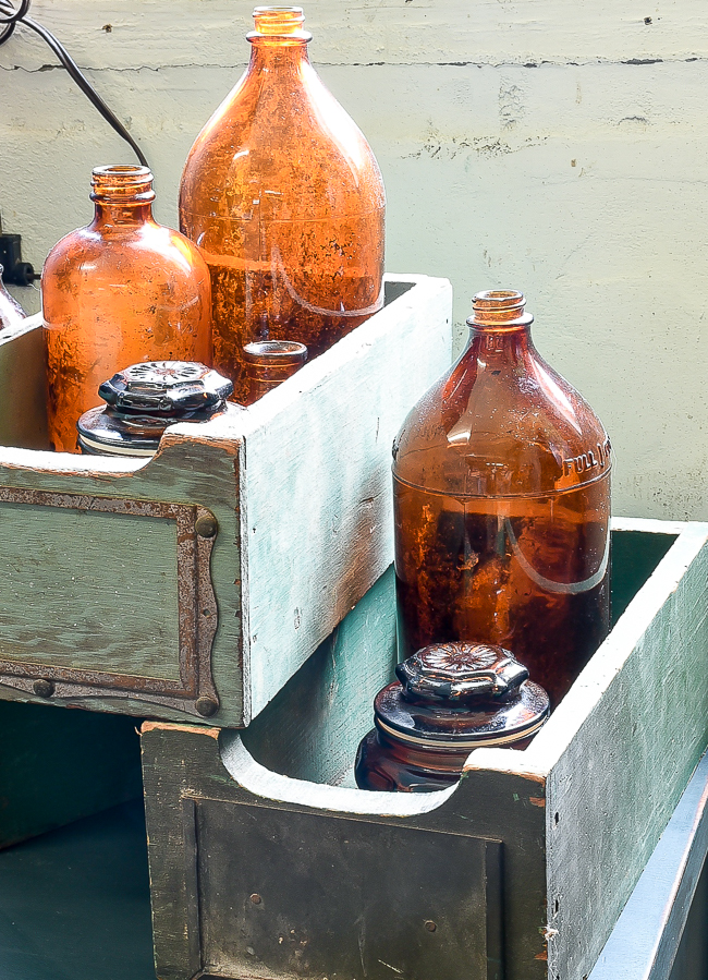 Vintage green boxes styled with antique amber bottles