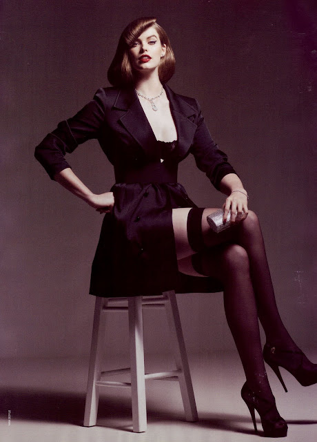 A plus sized model sits on a chair wearing a mid thigh coat and stockings