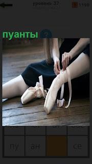 на полу балерина пытается одеть свои пуанты на ноги