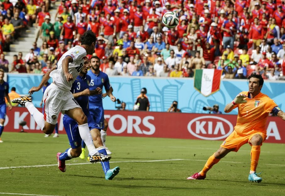 Costa Rica's Bryan Ruiz, left, heads the ball at Italy's goalkeeper Gianluigi Buffon to score his side's first goal during the group D World Cup soccer match between Italy and Costa Rica at the Arena Pernambuco in Recife, Brazil, Friday, June 20, 2014.