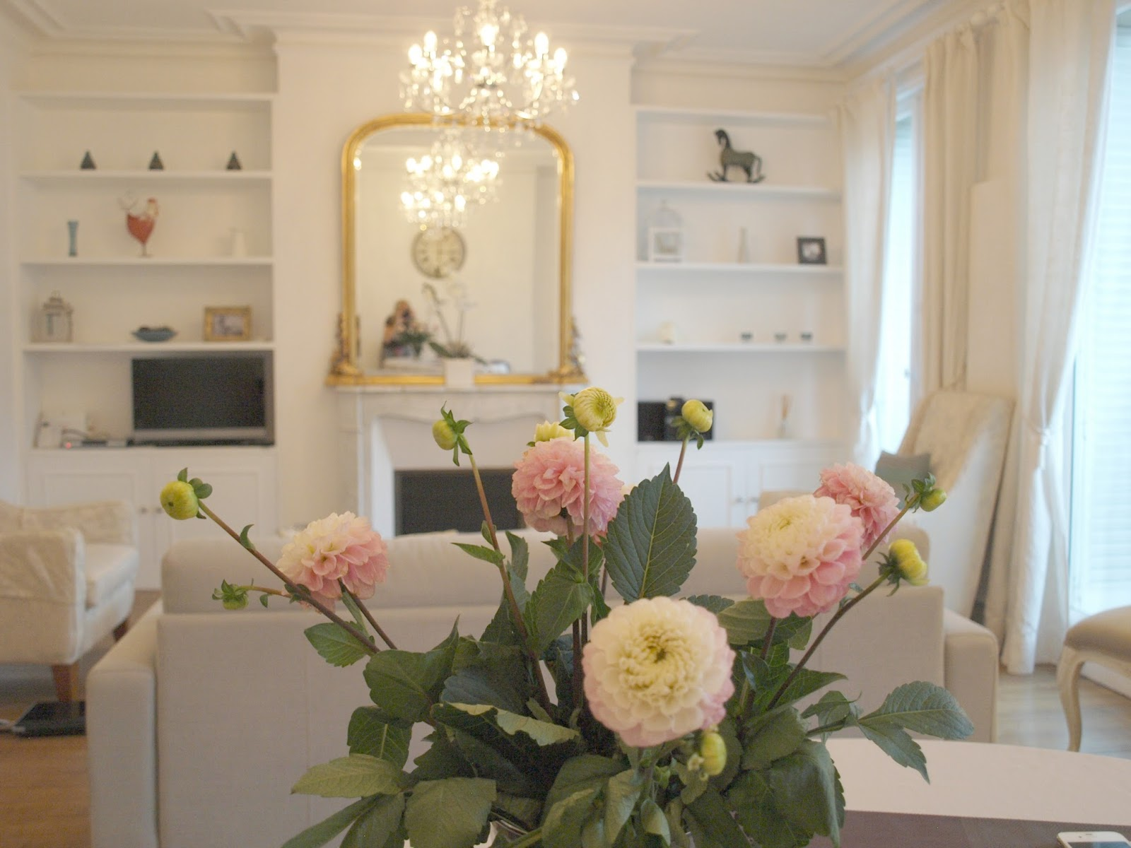 White living room in Paris apartment with open shelving and gorgeous pink floral arrangement - Hello Lovely