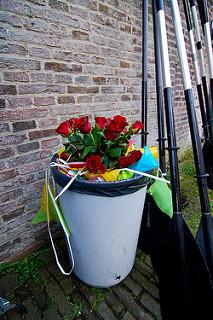 Ramo de rosas rojas en un cubo de basura