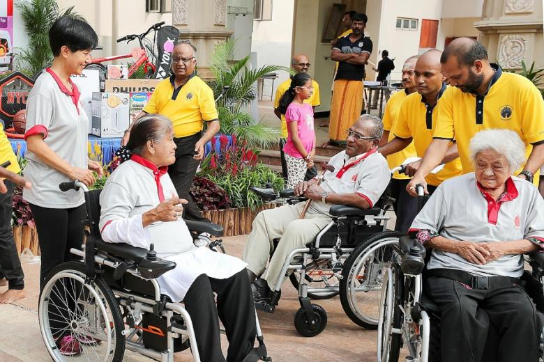 Minister in the Prime Minister's Office Indranee Rajah (far left) with some of the seniors who got a motorised wheelchair.