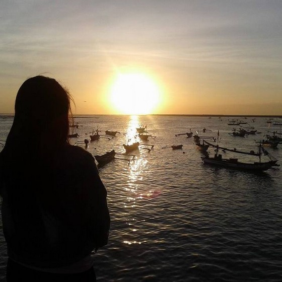 A girl looking at the sunset in Bali beach
