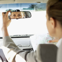 Woman looking back in a rearview mirror.
