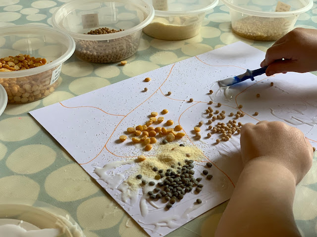Toddler gluing lentils and couscous onto card in sensory art idea