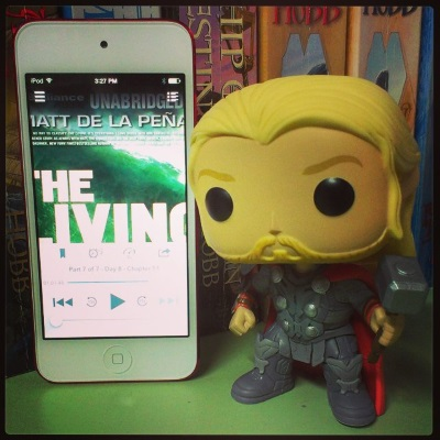 A small bobblehead of Thor dressed in grey armour and brandishing a warhammer stands beside a white iPod with The Living's cover on its screen. The cover features the title in large, white block letters against an oncoming wave. Much of it is obscured by the audio app's menu.