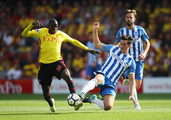 Lewis Dunk of Brighton and Hove Albion and Abdoulaye Doucoure of Watford battle for possession during the Premier League match between Watford and Brighton and Hove Albion at Vicarage Road on August 26, 2017 in Watford, England.