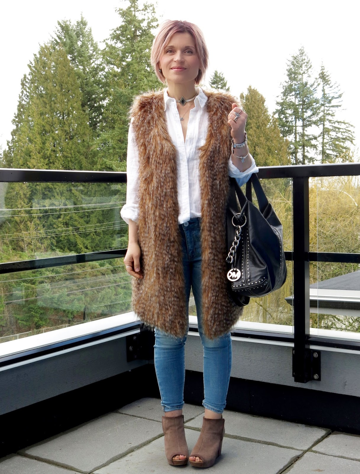 styling a white shirt and skinny jeans with a long, faux-fur vest and open-toe wedge booties