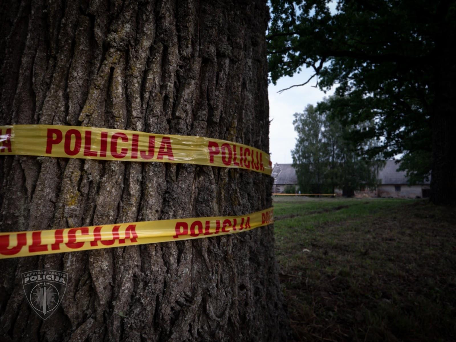 Policijas lenta aptīta ap koku, bet fonā redzama lauku māja