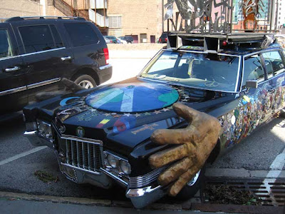 Cadillac art car with giant fins and a big paper mache hand on the side