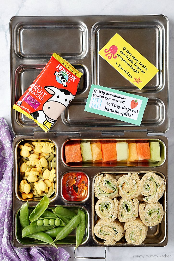 Free printable lunch box jokes for kids with a colorful packed lunch including cucumber cream cheese sandwich roll-ups.