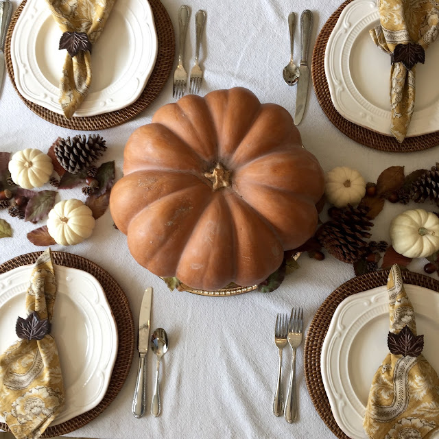 traditional fall tablescape with fairytale pumpkin, white pumpkins, acorns and pine cones