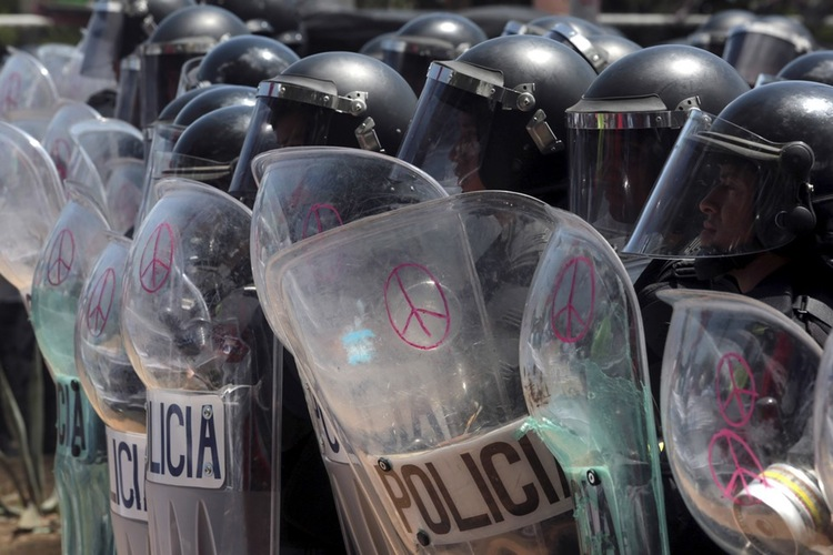 70 Of The Most Touching Photos Taken In 2015 - Police draw peace signs on their shields as protesters in Managua, Nicaragua, demanding fairer elections.