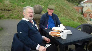 Two senior gentlemen take advantage of the good weather to visit the Clock Cafe, Scarborough, for breakfast