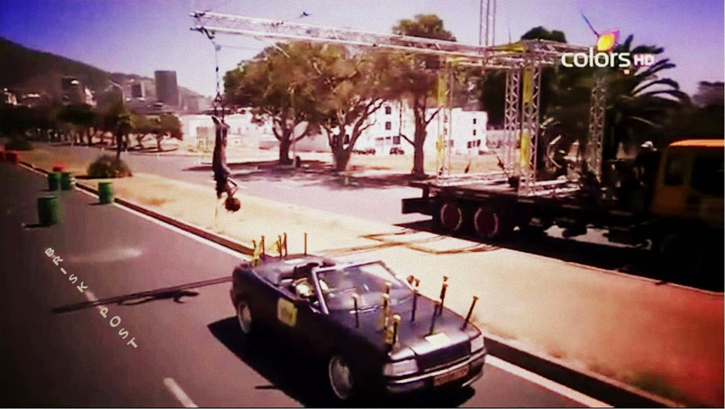 Hanging contestant collecting flags from slowly running car on street in Fear Factor Khatron Ke Khiladi