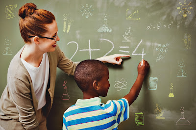Image of a female teacher teaching a student (boy) math at a chalkboard. He is learning 2+2=4
