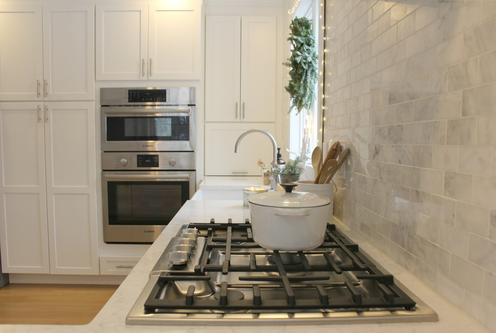 White European style kitchen with carrara marble statement wall and cooktop - Hello Lovely Studio