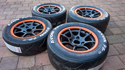 Orange rimmed, 8 spoke 13 inch R500 track day wheels with Avon ZZR tyres and painted tyre wall lettering