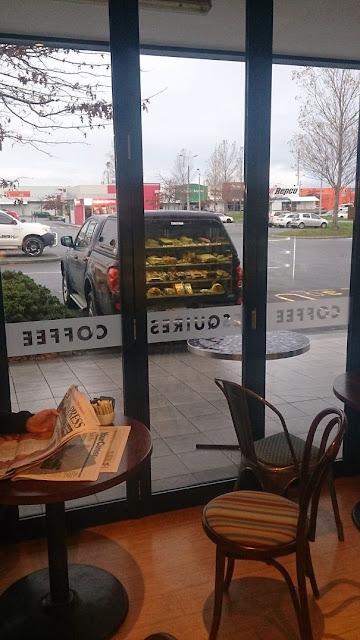 O reflexo da porta da loja de café faz com que pareça que este carro esta vendendo tortas com a porta aberta