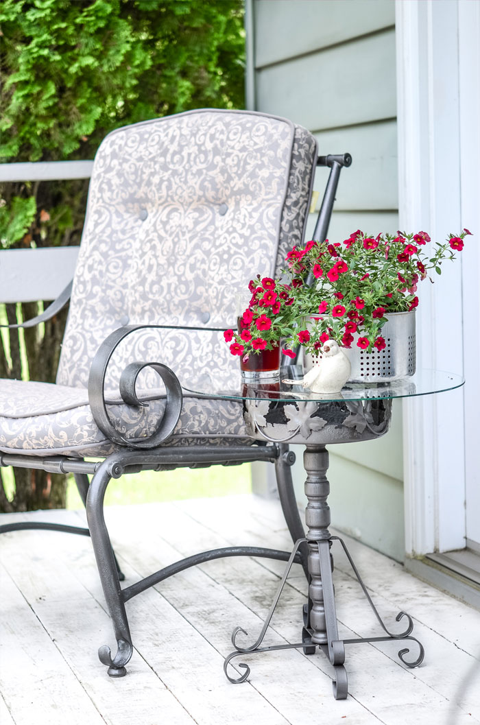 See how an old rusty plant stand can be repurposed as a useful accent table outdoors. #outdoortable #DIY #repurpose #metaltable