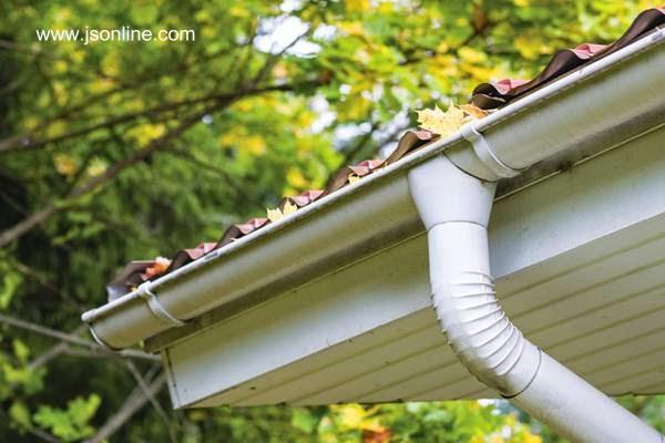 Canaleta de drenaje de agua de lluvia del techo obstruida con hojas de otoño