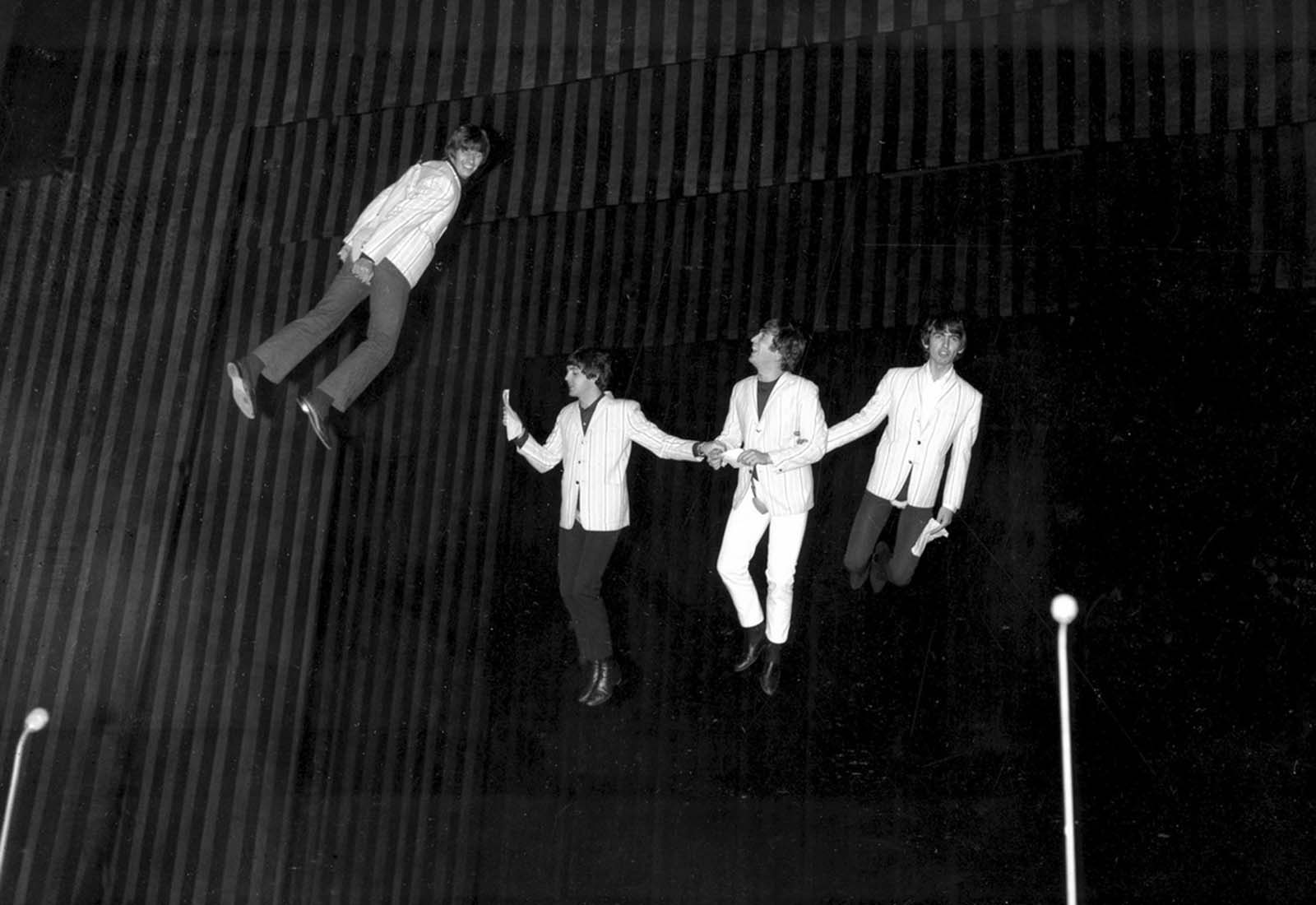 The Beatles are suspended in midair above the stage during rehearsal for their part in the charity show