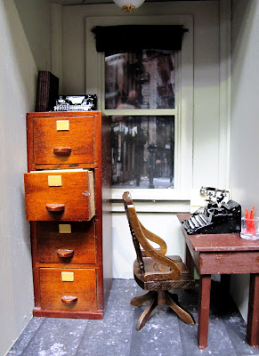 One-twelfth scale miniature 1940s office with filing cabinet, desk and typewriter.
