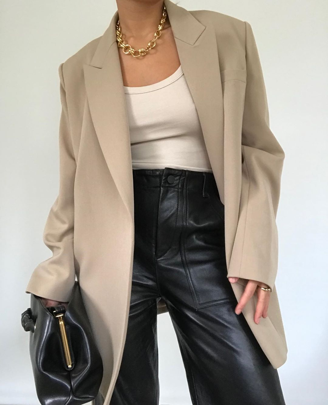 Minimalist Spring Outfit Idea: oversized beige blazer, a chunky chain necklace, off-white tank top, black pouch clutch, and black leather pants.