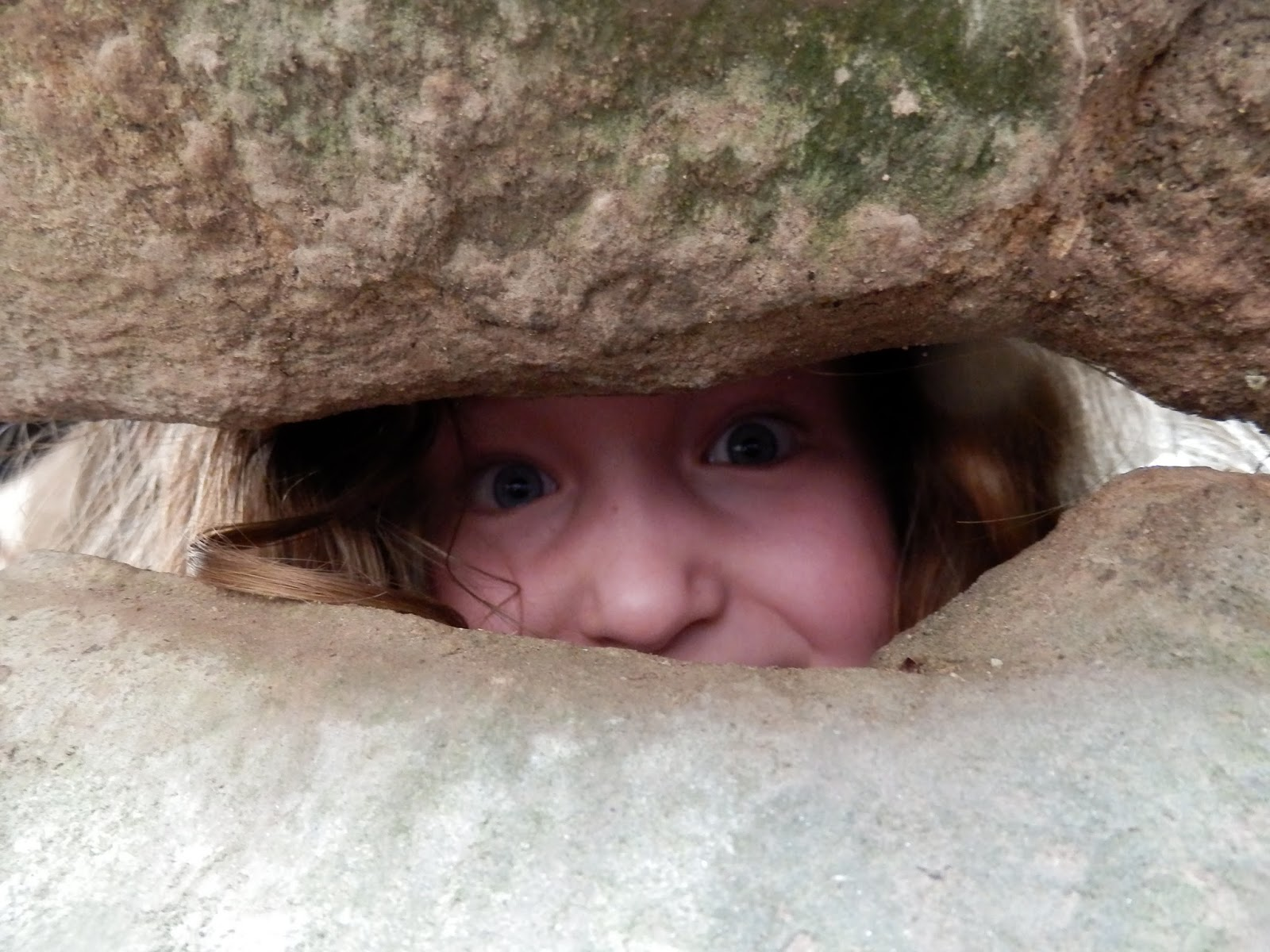 Caitlin peeping through a gap in the walls at Raglan Castle