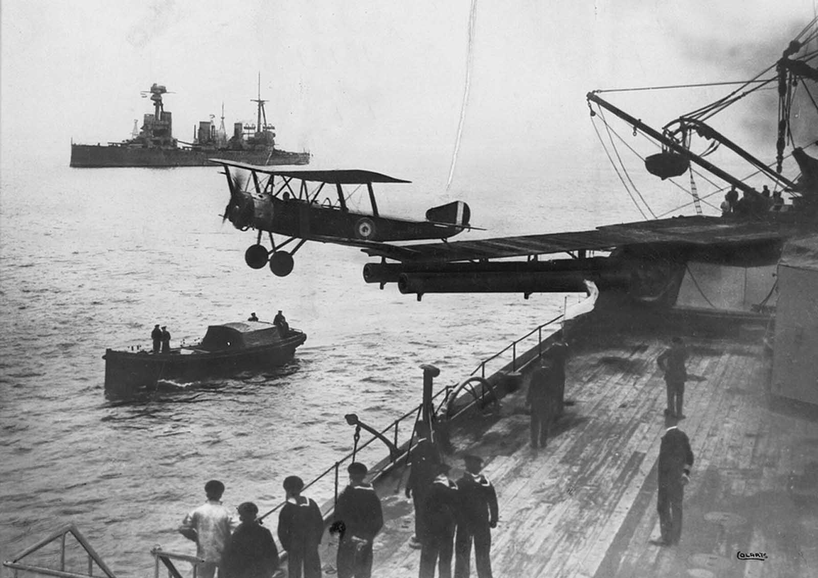 A Sopwith 1 1/2 Strutter biplane aircraft taking off from a platform built on top of HMAS Australia's midships