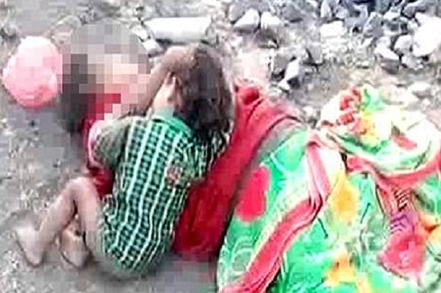 Seorang balita di India mencoba menyusu pada ibunya yang telah meninggal di pingir rel kereta api