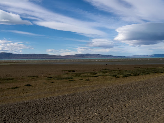 The sandy shore of Lago Argentina with glacial blue water beyond in El Calafate Argentina