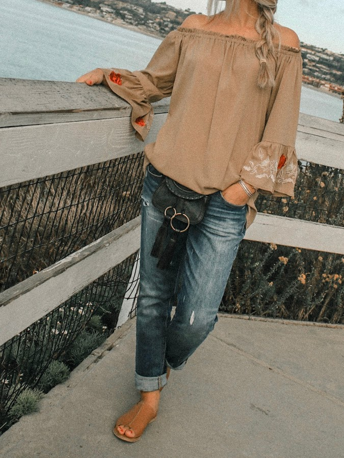 madewell boyfriend jeans off shoulder top outfit girl at the beach leather sandals see by chloe pouch bag
