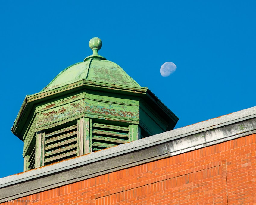Portland, Maine USA September 2017 photo by Corey Templeton. A glimpse of the moon beyond the cupola atop Lincoln Middle School.