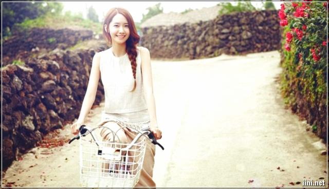cô gái vừa đạp xe đạp vừa cười
