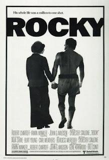 Cartel original de la película Rocky, 1976. Muestra al boxeador (S. Stallone) ataviado con su calzones, de la mano de una mujer, ambos de espaldas