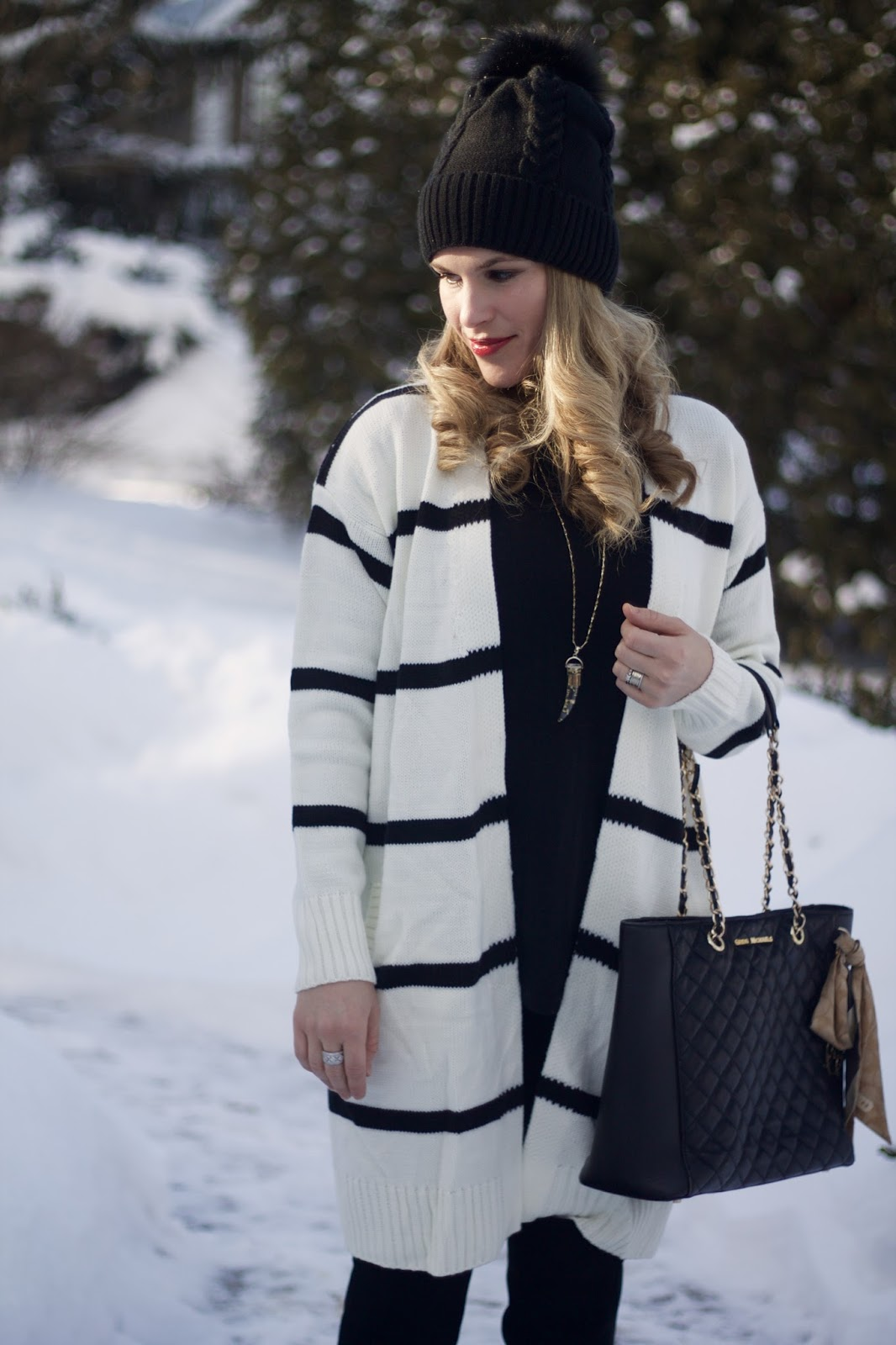 black jeans, black and white striped cardigan, black OTK boots, black quilted tote, black beanie with fur pom  pom
