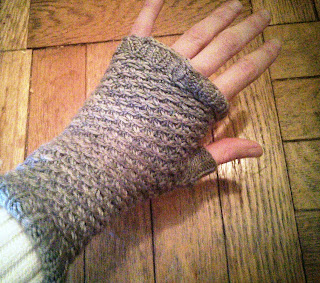 A blue textured fingerless mitten done in fingering-weight yarn.
