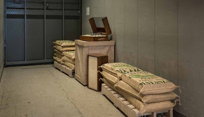 Image is of the inside of a frieght elevator. Stacks of sugar in cloth bags rest on pallets, surrounding an old record player on a crate.