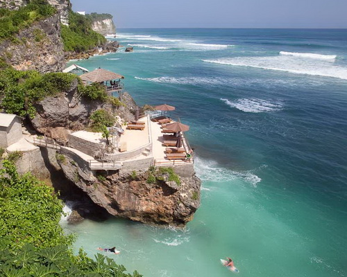 Travel.Tinuku.com Surfing Uluwatu beach riding 8 meters Indian Ocean waves in hidden spots under sacred temple cliffs